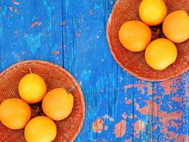 arance in una ciotola di vimini su uno sfondo di tavolo in legno foto