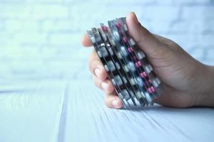 primo piano delle mani che tengono confezioni blister foto