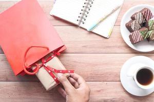 uomo che apre un regalo in borsa rossa foto