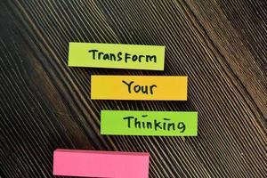 trasformare il tuo pensiero scritto su piccole note isolate su un tavolo di legno foto