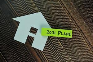 Piani 2021 fatti in casa da carta scritta su foglietti adesivi isolati su un tavolo di legno foto