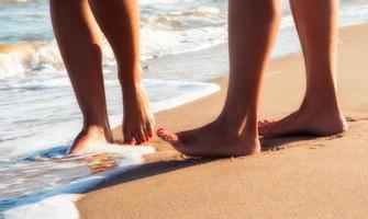 primo piano dei piedi nudi sulla sabbia foto