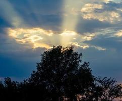 sole al tramonto e cielo blu foto