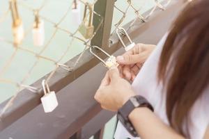 mano della donna che tiene un lucchetto su un recinto ferroviario ponte, serrature del concetto di amore foto