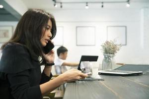 donna sul suo telefono in un caffè foto