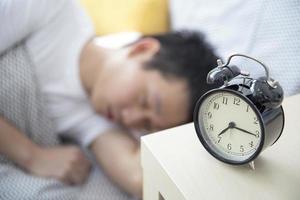 uomo addormentato con sveglia foto
