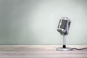 microfono retrò su uno sfondo verde con pavimento in legno foto