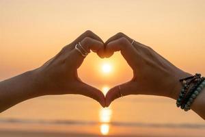 le mani della donna che fanno una forma del cuore su un cielo di tramonto e sul fondo del bokeh, concetto di giorno di San Valentino di amore foto
