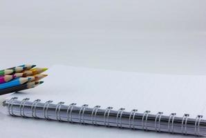 taccuino in bianco isolato con matite colorate foto