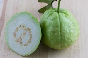 mezzo guava affettato su uno sfondo di legno foto