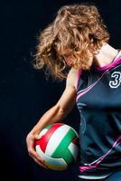 donna con una palla da pallavolo su sfondo nero foto