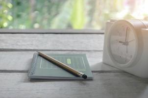 libro verde, matita e sveglia su un tavolo di legno bianco foto
