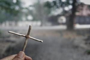 mano che tiene una croce di gesù cristo in una tomba. simbolo della fede nella religione del cristianesimo foto