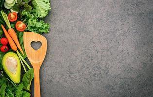 cibo sano e concetto di cucina con una spatola di legno e verdure su sfondo di pietra scura. foto