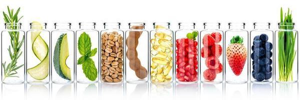 cura della pelle fatta in casa con ingredienti di frutta di avocado, arancia, mirtillo, melograno, kiwi, limone, cetriolo, tamarindo, fragola e lampone in bottiglie di vetro isolate su uno sfondo bianco. foto