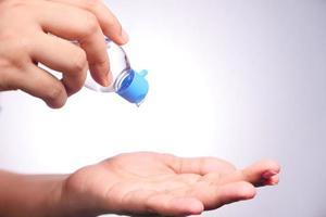 mano utilizzando gel igienizzante su sfondo bianco foto