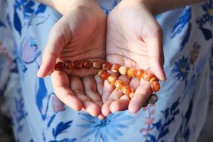 primo piano delle mani della donna che prega con perline foto
