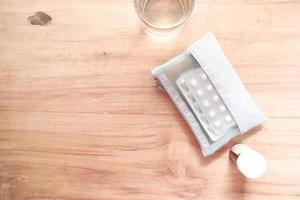 confezioni blister e acqua sul tavolo di legno foto