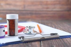 stetoscopio e contenitore di pillole negli appunti foto