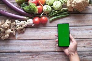smart phone con schermo verde su fondo in legno con un sacco di verdure fresche foto
