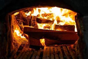 primo piano massa di legna da ardere che brucia nella stufa tradizionale con posacenere foto