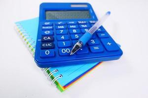 Close up blu calcolatrice e blocco note foto