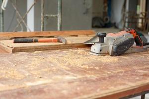 messa a fuoco selettiva sugli strumenti di falegnameria sulla scrivania in legno sporco con segatura foto
