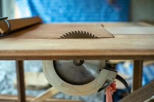 primo piano del piatto di metallo della macchina sega elettrica nel tavolo in fabbrica foto