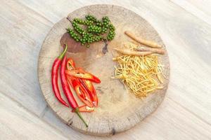 foto vista dall'alto di peperoncino, fingerroot e pepe sul piatto di legno