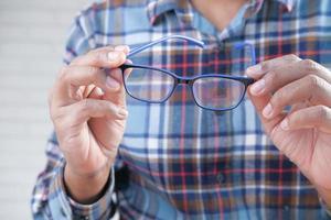 mano dell'uomo che tiene gli occhiali foto