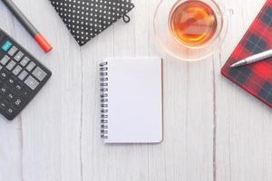 aprire il blocco note e le penne sulla scrivania bianca foto