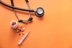 stetoscopio, pillole e siringhe su sfondo arancione foto