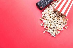 popcorn e telecomando della tv su sfondo rosso foto