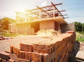 mucchio di mattoni rossi con casa sfocata in costruzione foto