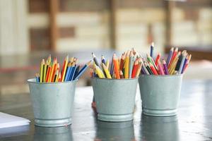 primo piano di matite colorate smussate in secchi di metallo foto