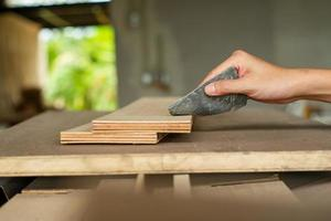 messa a fuoco selettiva su una mano di falegname che strofina la superficie del legno in fabbrica foto
