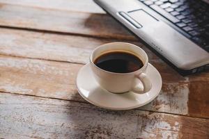 caffè e piattino con un computer portatile foto