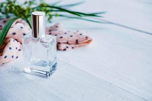 bottiglia di profumo con nastro e pianta