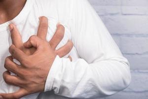 giovane che soffre di dolore al cuore e tenendo il petto con la mano foto
