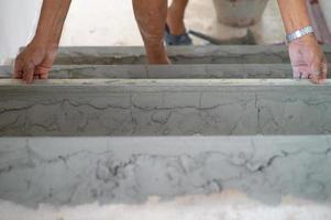 primo piano le mani del lavoratore lavora con cazzuola in pavimento di cemento intonacato foto