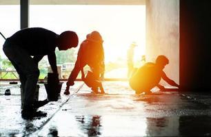 silhouette gruppo di lavoratori costruire il pavimento di cemento nella casa in costruzione foto