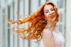 giovane ragazza dai capelli rossi che cammina in un parco tra alberi e oggetti architettonici
