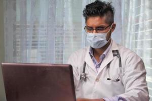medico in maschera protettiva utilizzando laptop in ospedale foto