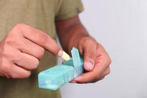 stretta di mano uomo prendendo pillole dalla scatola della pillola foto