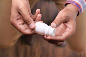 stretta di mano di una persona che tiene il contenitore della pillola foto