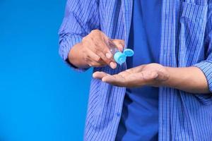 uomo che utilizza un disinfettante per le mani di viaggio foto