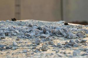 trama e lo sfondo del mucchio di pietra si è schiantato in cantiere con la luce del tramonto foto