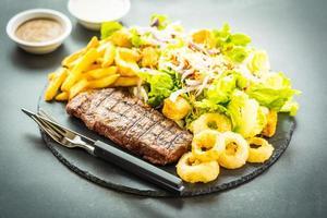 bistecca di carne di manzo alla griglia con patatine fritte anello di cipolla con salsa e verdura fresca