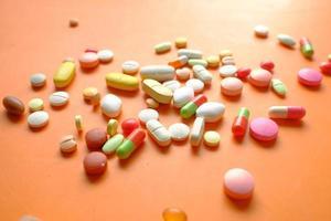 Close up di molte pillole colorate e capsule che si rovesciano su sfondo arancione foto