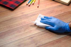 mano in guanti di gomma blu che disinfettano la superficie del tavolo foto